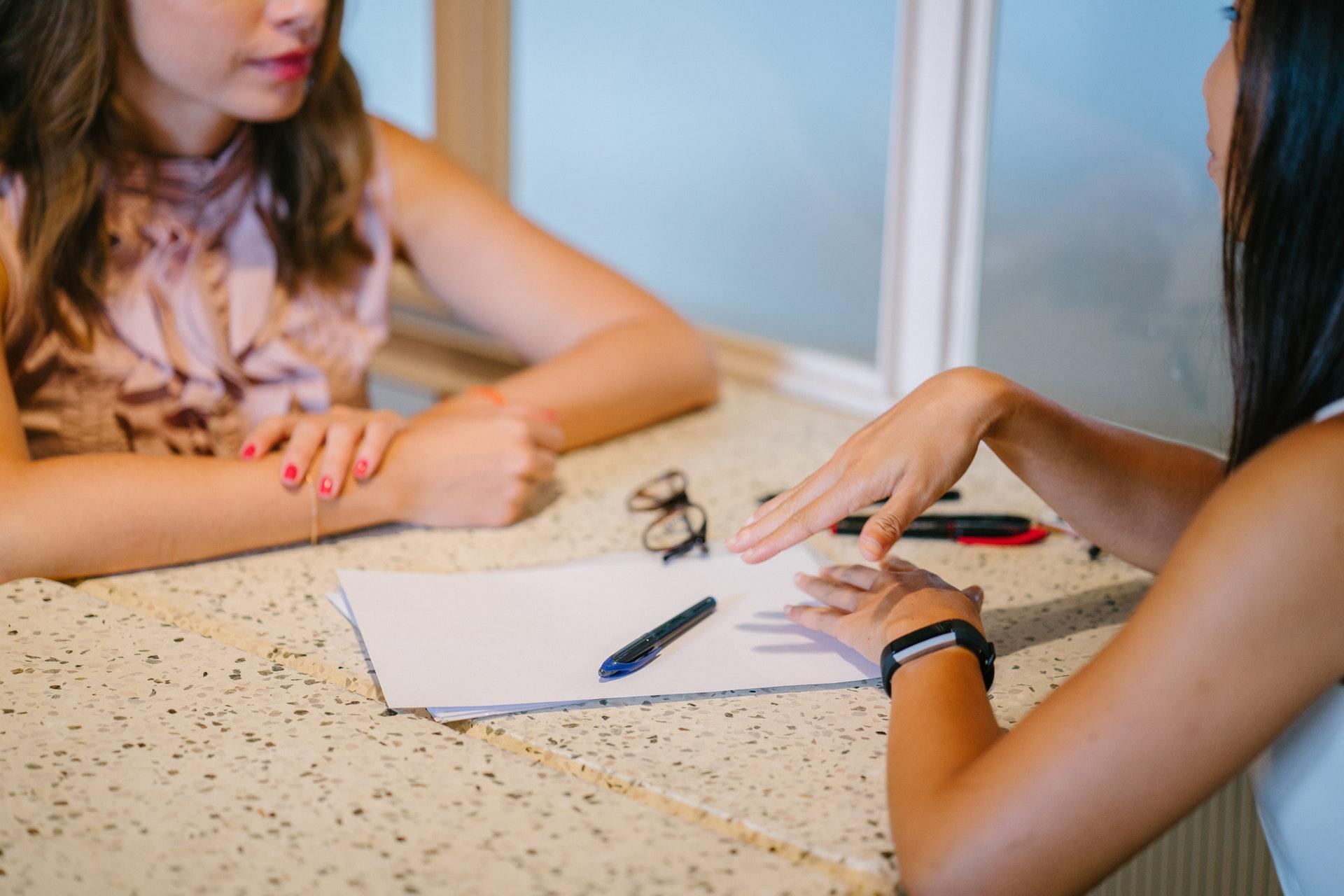 Två kvinnor pratar vid ett bord